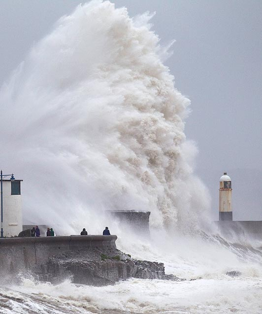 Huge waves break over the lighthouse at Porthcawl seafront in South Wales