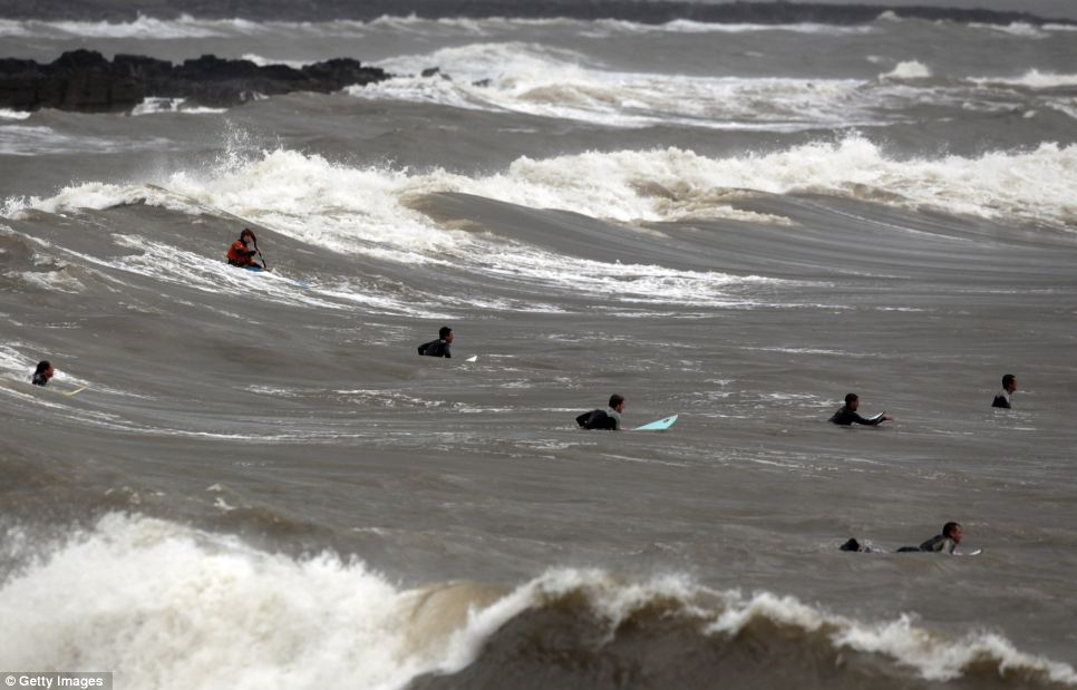Surfers take advantage of stormy seas caused by a low pressure weather system in Porthcawl