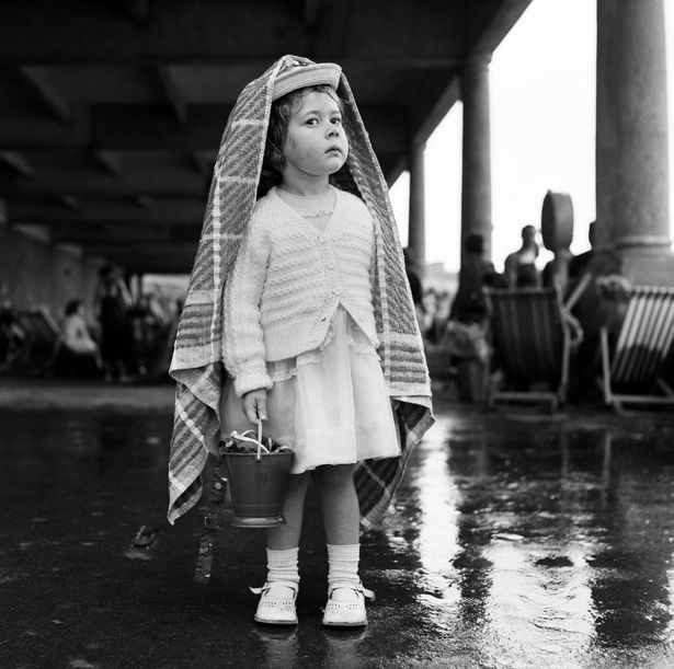 A small girl shelters from the rain at Barry Island in 1960
