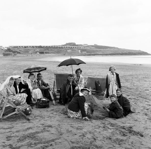 Families shelter from the rain under blankets and umbrellas on the beach at Barry in 1960