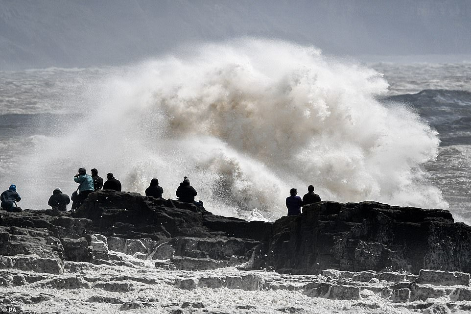 People watch huge stormy waves crash against the shore at Porthcawl, Wales, where Storm Hannah hit yesterday