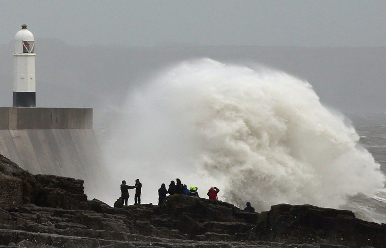 People stand on the rocks as large waves break against barriers at the harbor in Porthcawl, south Wales on October 27, 2013 as a predicted storm starts to build. Britain was braced on October 27 for its worst storm in a decade, with heavy rain and winds of more than 80 miles an hour set to batter the south of the country. (Geoff Caddick/AFP/Getty Images)