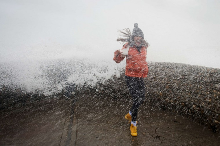 A woman is soaked as large waves crash against the walls of Brighton seafront, in southern England on October 27, 2013 as a predicted storm starts to build. Britain was braced on October 27 for its worst storm in a decade, with heavy rain and winds of more than 80 miles an hour set to batter the south of the country. (Leon Neal/AFP/Getty Images)