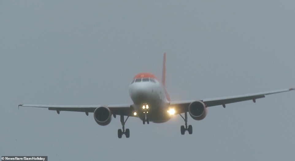 Aircraft over Liverpool Airport were pictured struggling to touch down yesterday as strong winds continue across the country