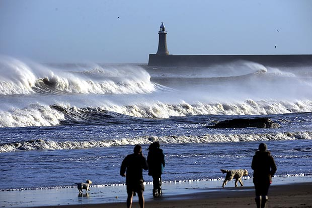 People walk during high winds at Tynemouth beach, Tyne and Wear.