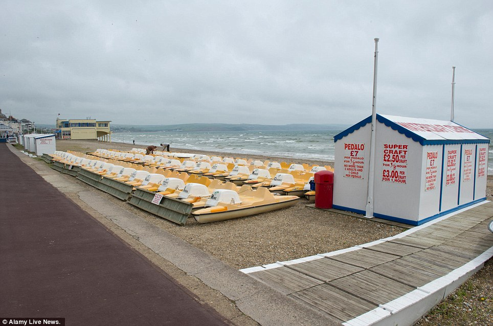 Empty: The dreadful weather conditions have affected the tourist industry. These pedalos wait to be hired on a bleak-looking beach in Weymouth, Dorset