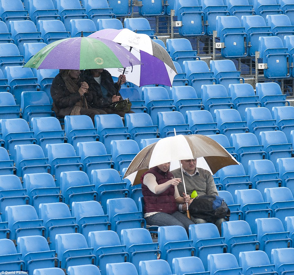 Grim: Spectators take cover under umbrellas yesterday after rain stopped play at the Aegon tennis championships at Queen's club in London