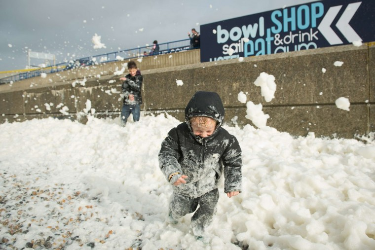 Will Brewer, 4, plays in the foam washed ashore on the Brighton seafront on October 27, 2013, as high winds pick up ahead of an expected storm. Britain was braced on October 27 for its worst storm in a decade, with heavy rain and winds of more than 80 miles (130 kilometers) an hour set to batter the south of the country. (Leon Neal/AFP/Getty Images)