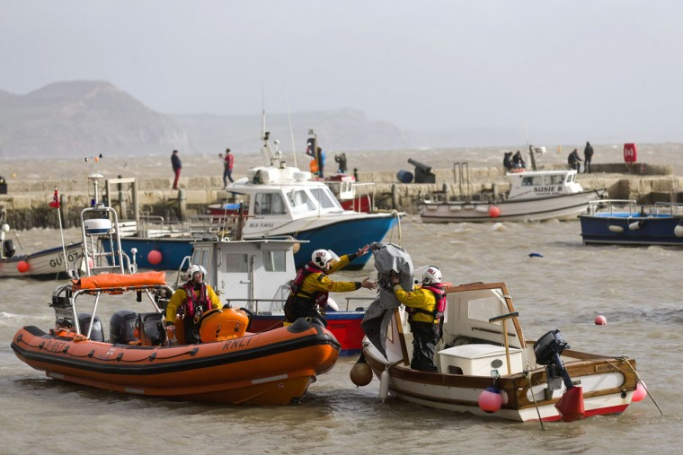 Royal National Lifeboat Institution (RLNI) workers check boats in a harbour in Lyme Regis, southern England on October 27, 2013 in preparation for an expected storm. Britain was braced on October 27 for its worst storm in a decade, with heavy rain and winds of more than 80 miles an hour set to batter the south of the country. (Justin Tallis/AFP/Getty Images)