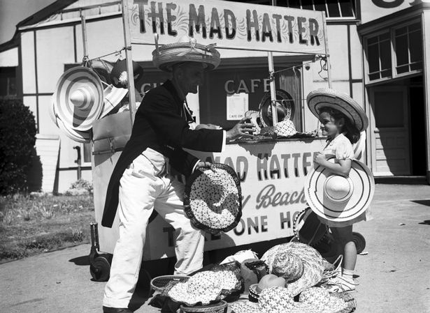 A young girl trying on a hat at 'The Mad Hatter' stall in Barry Island in 1951