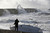A boat lays stricken on the strand as people watch the waves batter into the sea wall of a marina in Brighton, south England, Monday, Oct. 28, 2013.  (AP Photo/Sang Tan)