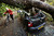 A car is crushed under a fallen tree as a man pushes a bicycle nearby following a storm, in Hornsey, north London, Monday Oct. 28, 2013. (AP Photo/PA, Yui Mok)