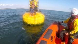 RNLI boat approaches stranded kayaker on a buoy off Porthcawl, Bridgend