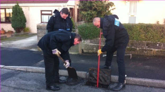 Police checking the drains in the street