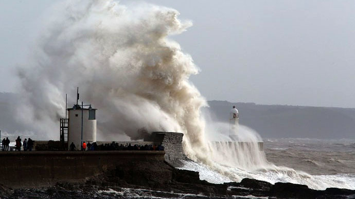 People look on as high waves strike the harbour wall at Porthcawl, south Wales on February 8 2014. (AFP Photo / Geoff Caddick)