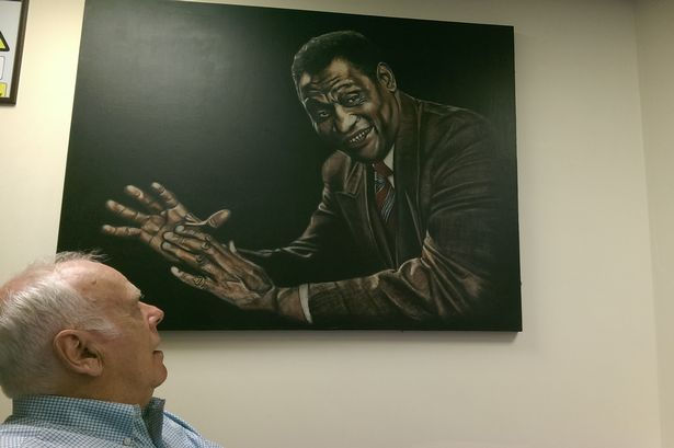 Roger Price, organiser of the South Wales Miners Eisteddfod, with a portrait of American singer, actor and civil rights activist Paul Robeson at the Grand Pavilion in Porthcawl