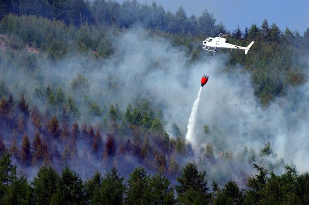 A helicopter dumps water on a fire in Wattsville